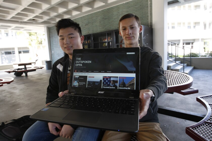 La Cañada High School juniors Ethan Kim, 16, left, and contributor Mason Pirkey, 16, display the homepage of their site the Outspoken Oppa, which aims to create a marketplace of ideas among students of varying beliefs.