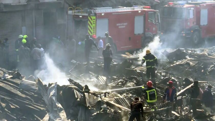 In this image from TV, a fire fighter damps down the charred debris after a fire swept through a mar
