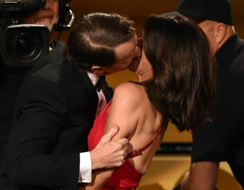 Bryan Cranston, who won the Emmy for lead actor in a drama, plants one on Julia Louis-Dreyfus, who won the Emmy for lead actress in a comedy, at the 2014 awards ceremony Monday.