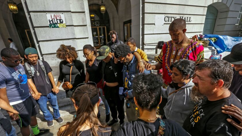 Black Lives Matter members and other supporters protesting the police shooting of Redel Jones offer prayers in front of Los Angeles City Hall.