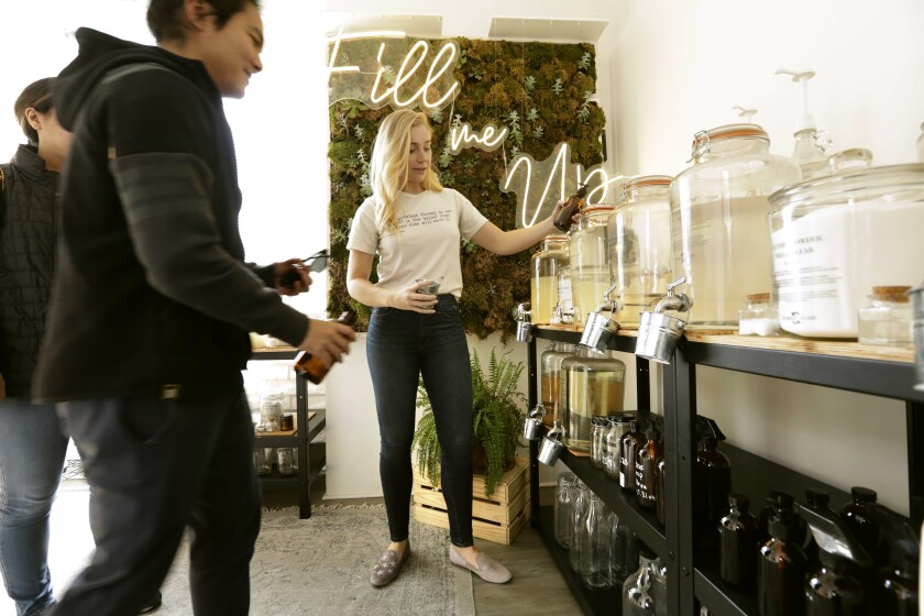Stephanie Cochrane, founder of the Waste Less Shop in Manhattan Beach, helps at her store's refill station.
