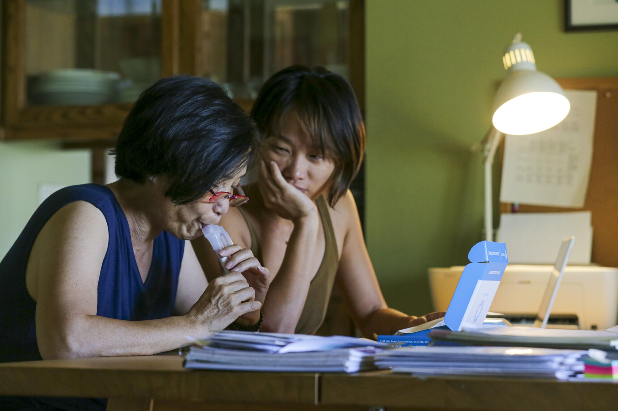 Yi Luo, right, watches her 63-year-old mother Yuyuan Lin, collect a saliva specimen for a  test.