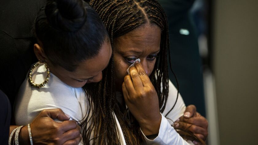 Pride Franklin, left, hugs Cherie Townsend after speaking during a news conference Monday. Townsend was accused of murder after visiting the Promenade on the Peninsula shopping center the same day retired nurse Susan Leeds, 66, was found stabbed in her Mercedes in May.