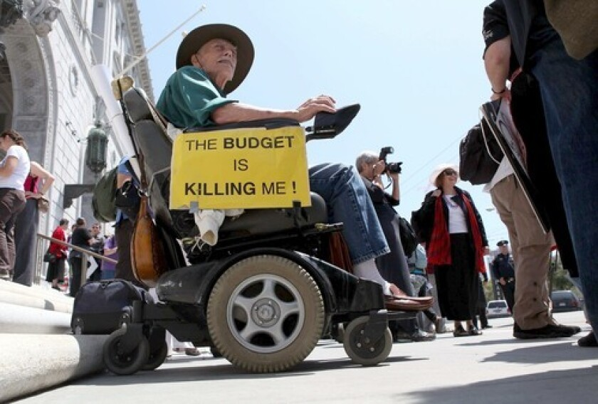 In San Francisco, a man in a wheelchair protests proposed budget cuts.