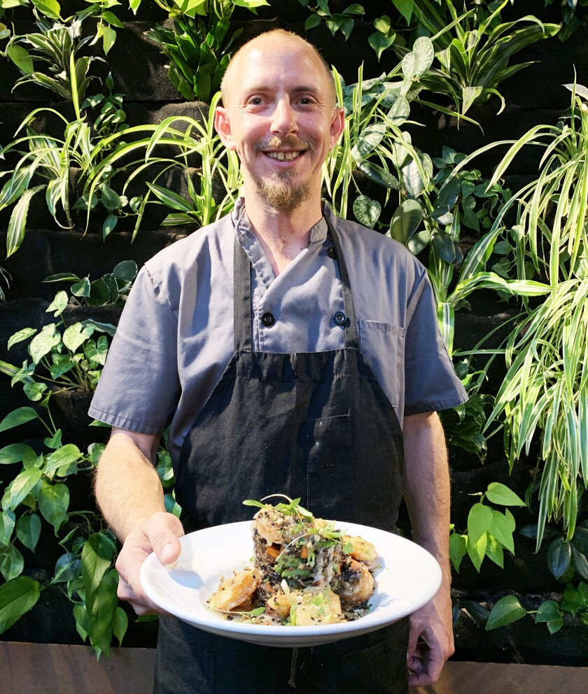 Mario Manship, the executive chef at Masters Kitchen and Cocktail in Oceanside, with one of the dishes on his new menu rolling out Nov. 1: honey pecan shrimp with forbidden black rice and fried pork belly bites.
