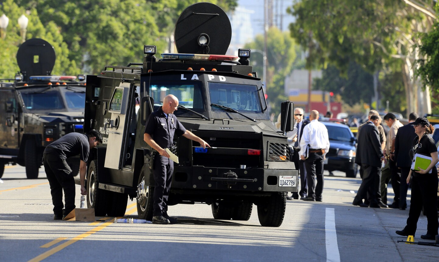 Los Angeles Police Cmdr. Andrew Smith looks at the damage to an LAPD BearCat, a wheeled armored personnel carrier, after an officer involved shooting that killed a man early Monday morning.