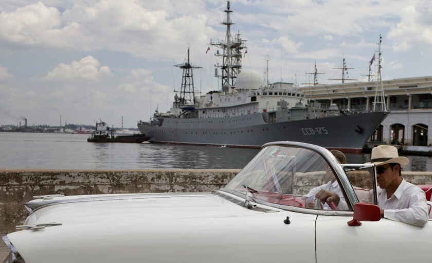 An American classic car passes in front of the Russian warship, The Viktor Leonov CCB-175, docked in Havana's harbor in Havana, Cuba. Despite the absence of official diplomatic relations, Cuba remains a major component of U.S. foreign policy.