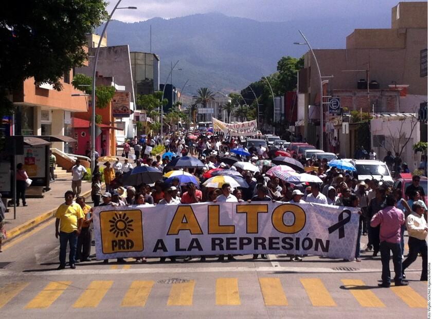 Con mantas en las que pidieron un alto a la represión, militantes del PRD marcharon ayer por calles de Oaxaca.