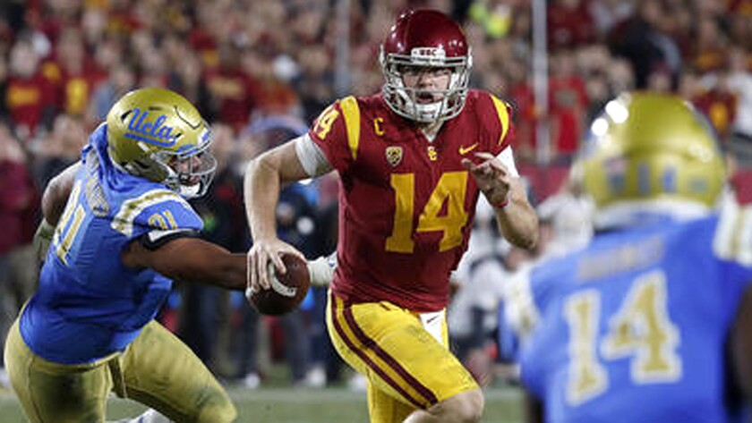 USC quarterback Sam Darnold scrambles out of the pocket and away from UCLA defensive lineman Jacob Tuioti-Mariner in the closing seconds of the second quarter on Nov. 18.