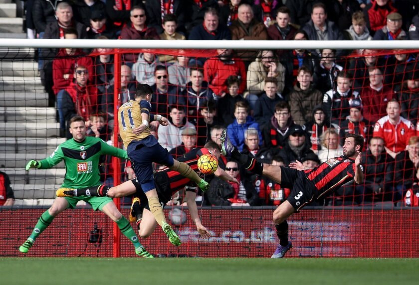 Arsenal's Mesut Ozil scores his side's first goal of the game, during the English Premier League soccer match between Bournemouth and Arsenal,  at the Vitality Stadium, in Bournemouth, England, Sunday Feb. 7, 2016. (John Walton/PA via AP) UNITED KINGDOM OUT