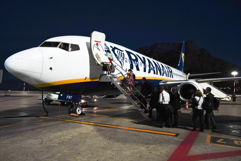 Passengers board a Ryanair airplane, in Palermo, Italy, Saturday, Sept. 15, 2018. Italy's aviation authority, ENAC, has put RyanAir on notice that it has ''repeatedly violated'' rules aimed at curbing the spread of coronavirus, warning that the budget carrier risks suspension in Italy unless it complies. ENAC said in a statement Wednesday, Aug. 5, 2020 that RyanAir had repeatedly disregarded rules, calling it ''behavior disrespectful of the health measures in Italy.'' They include requiring passengers to wear masks, restricting baggage on board to small items placed in plastic bags and preventing crowding at baggage pickup. (AP Photo/Andrew Medichini)