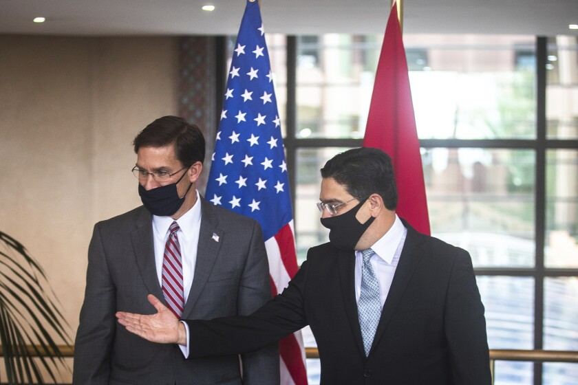 US Secretary of Defense Mark Esper, left, is received by Moroccan Foreign Minister Nasser Bourita, right, in Rabat, Morocco, Friday, Oct. 2, 2020. The visit is part of US Defense Secretary Mark Esper's North Africa tour and is his first visit to Africa as defense secretary. (AP Photo/Mosa'ab Elshamy)