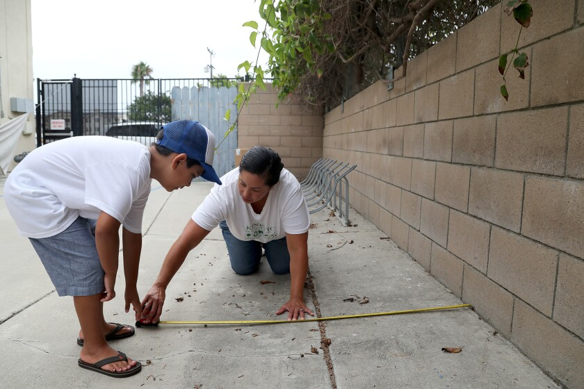 Daya Oyarzabal and her son, Salvador, work on plans to build a raised bed butterfly garden at Kinetic Academy.