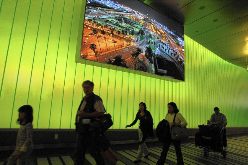 Travelers arrive at the Tom Bradley International Terminal where they are greeted by high-tech lighting and a video screen.