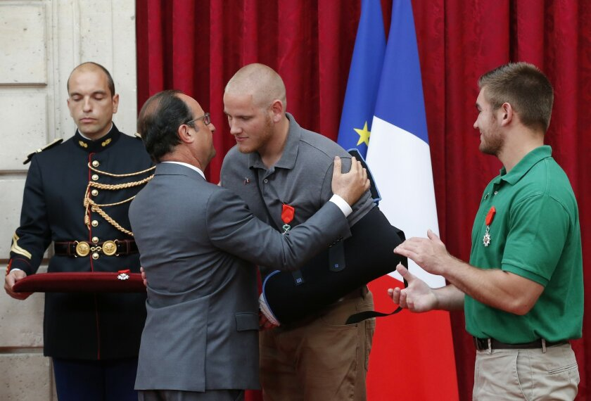 French President Francois Hollande, second left, hugs U.S. Airman Spencer Stone, center, while Alek Skarlatos a U.S. National Guardsman from Roseburg, Oregon applauds after they were awarded with the Legion of Honor at the Elysee Palace, Monday Aug.24, 2015 in Paris, France. Hollande pinned the Legion of Honor medal on U.S. Airman Spencer Stone, National Guardsman Alek Skarlatos, and their years-long friend Anthony Sadler, who subdued the gunman as he moved through the train with an assault rifle strapped to his bare chest. The British businessman, Chris Norman, also jumped into the fray. (AP Photo/Michel Euler, Pool)