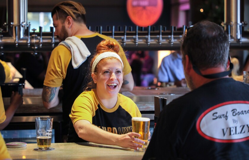 At a private preview party at My Yard Live bartender Kelly Stack serves a beer to a customer.