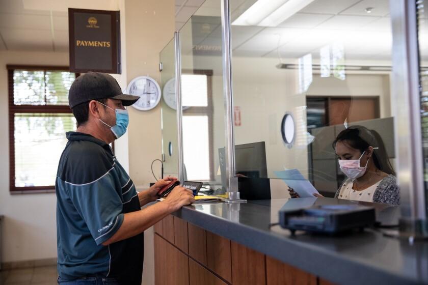 John Padilla speaks with cashier Jessi Galicia at Chula Vista City Hall's Finance Department on Wednesday.