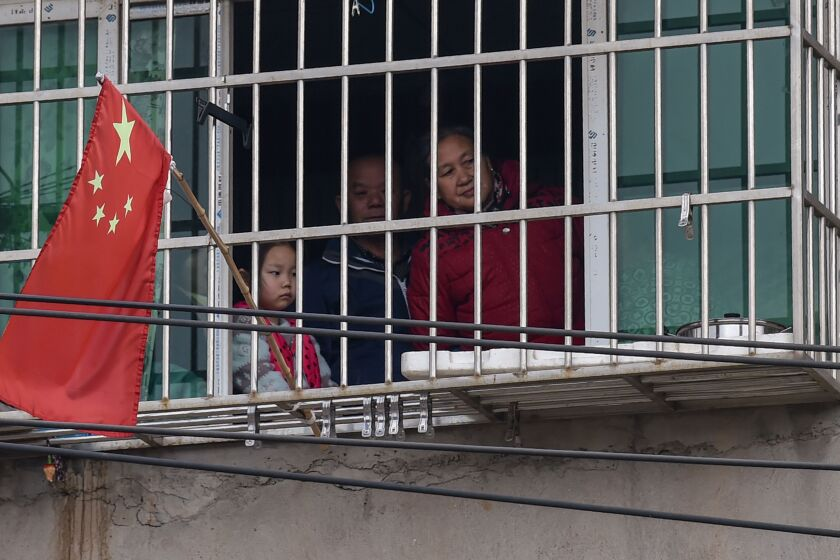 A family looks out the window of their home in a neighborhood on the outskirts of Wuhan.