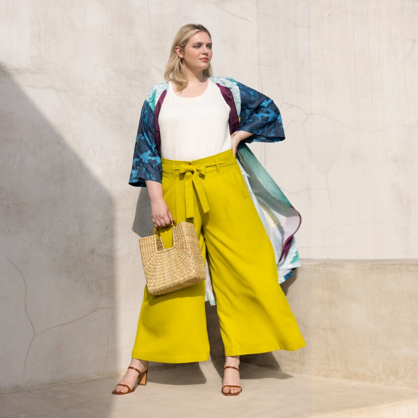A woman modeling wide-leg yellow pants and a beach-inspired wrap