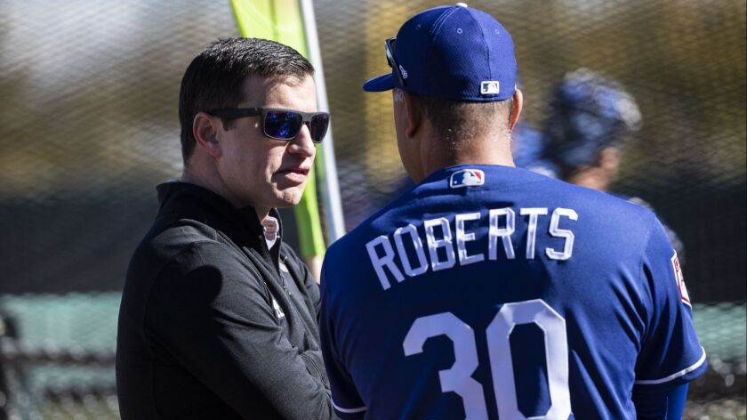 Dodgers Manager Dave Roberts, right, talks with the President of Baseball Operations Andrew Friedman during spring training at Camelback Ranch