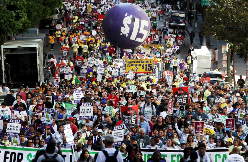 Workers march through the financial district in downtown Los Angeles to press for a minimum wage of $15 per hour on Nov. 10, 2015.