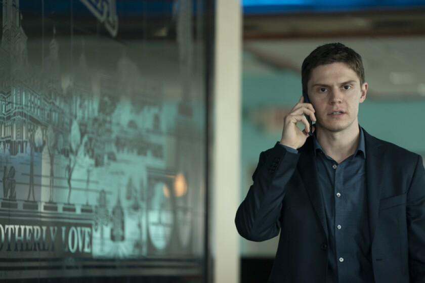 """Actor Evan Peters talks on his cell next to a """"City of Brotherly Love"""" mural in a scene from """"Mare of Easttown."""""""