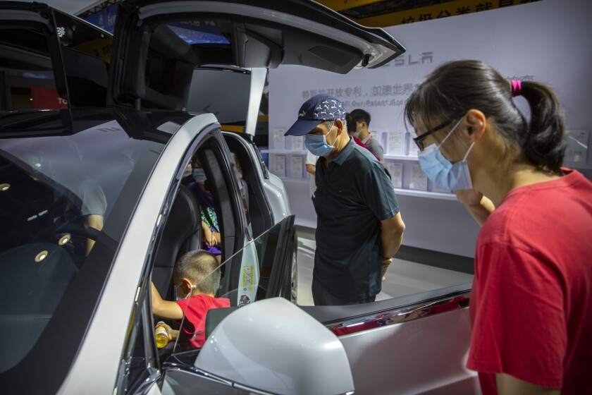 Visitors wearing face masks to protect against the coronavirus look at a Tesla vehicle on display at the China International Fair for Trade in Services (CIFTIS) in Beijing, Saturday, Sept. 5, 2020. Auto executives are flying in early to wait out a coronavirus quarantine ahead of the Beijing auto show, the year's biggest sales event for a global industry that is struggling with tumbling sales and layoffs. Organizers say they will impose intensive anti-disease controls on crowds and monitor visitors and employees for signs of infection. (AP Photo/Mark Schiefelbein)