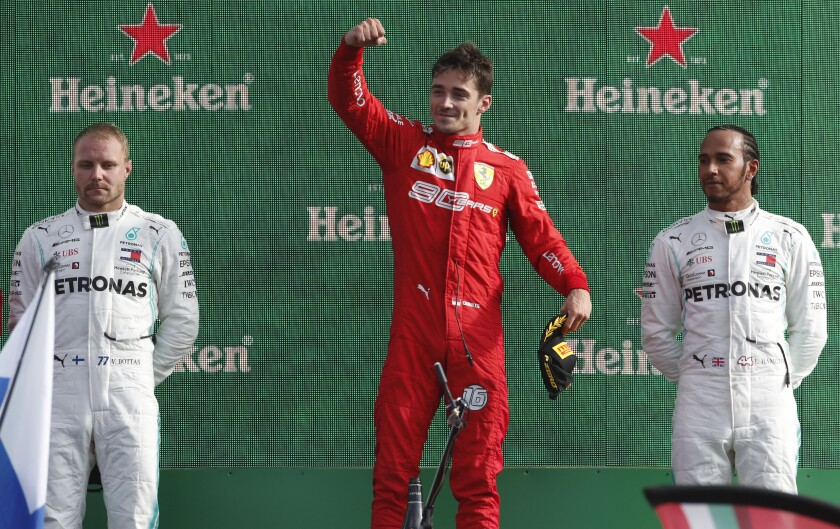 Ferrari driver Charles Leclerc, flanked by Mercedes drivers Valtteri Bottas, left, and Lewis Hamilton, right, celebrates on the podium after winning the Italian Grand Prix on Sunday.