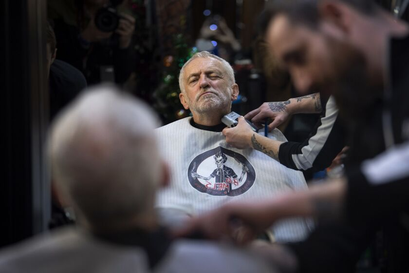 FILE - In this Saturday, Dec. 7, 2019 file photo Labour Party leader Jeremy Corbyn has his beard trimmed in Big Mel's Barbershop, Carmarthen, while on the General Election campaign trail in Wales. (Victoria Jones/PA via AP, File)