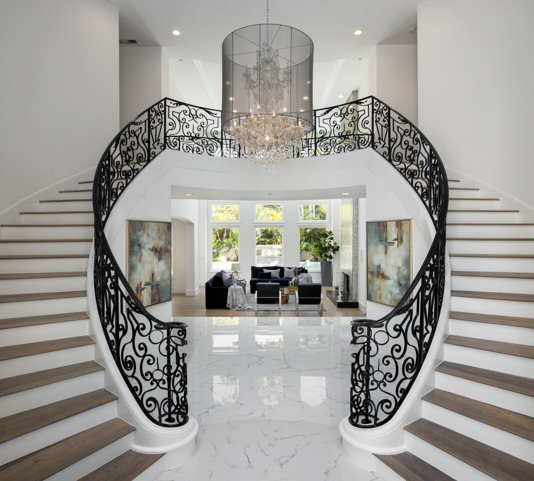 Built in 2000, the two-story home in Mulholland Park holds seven bedrooms, seven bathrooms, a dramatic foyer with dual staircases and a two-story living room with a floor-to-ceiling fireplace.