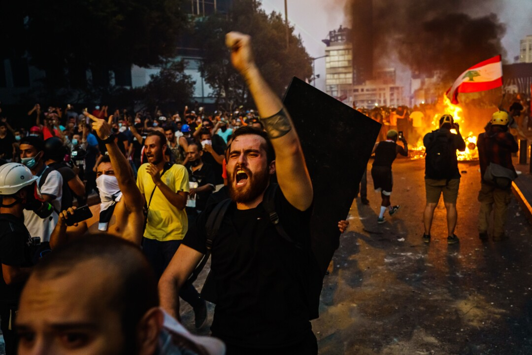 A dense crowd of people march, lifting their arms and shouting; a fire burns on the street in the background.