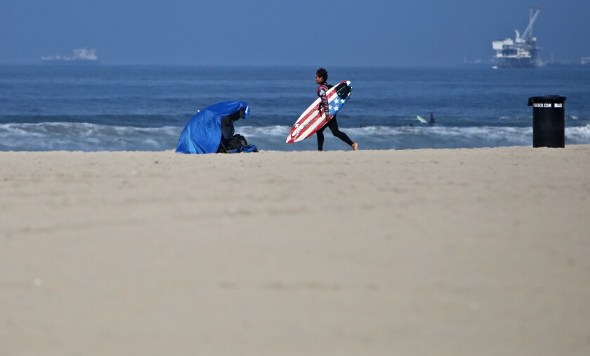 A surfer carrying a surfboard crosses the almost empty beach to catch some waves in Huntington Beach on May 2.