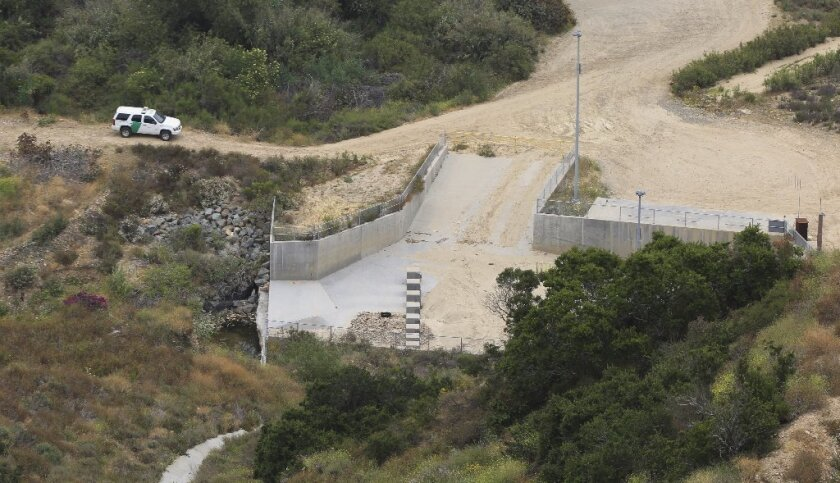 Border Patrol vehicle in Smuggler's Gulch at the U.S.-Mexican border in San Diego where a culvert em