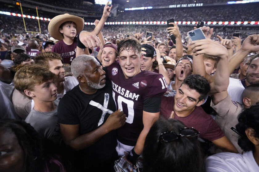 Texas A&M quarterback Zach Calzada is surrounded by fans after beating Alabama