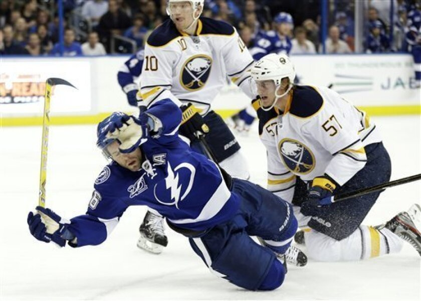 Tampa Bay Lightning right wing Martin St. Louis (26) gets tripped by Buffalo Sabres defenseman Tyler Myers (57) during the second period of an NHL hockey game Tuesday, Feb. 26, 2013, in Tampa, Fla. Myers was penalized on the play. (AP Photo/Chris O'Meara)