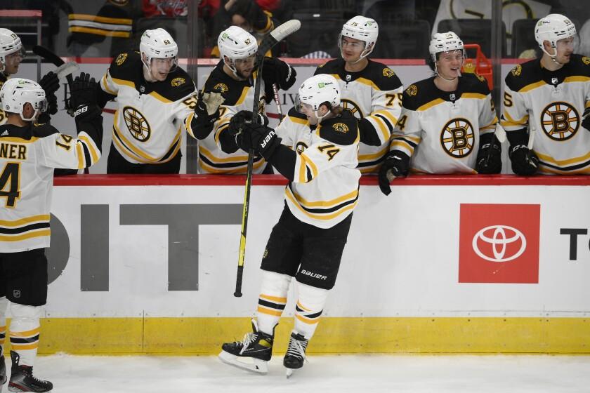 Boston Bruins left wing Jake DeBrusk (74) celebrates his goal during a shootout of an NHL preseason hockey game against the Washington Capitals, Sunday, Sept. 26, 2021, in Washington. (AP Photo/Nick Wass)
