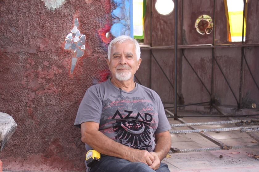 Nasser Pirasteh sits in front of his installation, moments before crews cut into it to move it.
