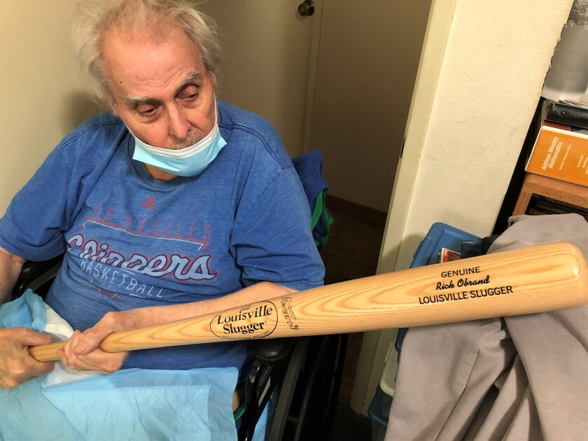 Rick Obrand holds his own autographed Louisville Slugger bat at his home.