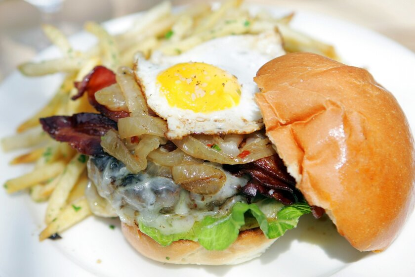 The Whisknladle Burger: artisan cheese, bacon, caramelized onions and a fried egg) served with fries.
