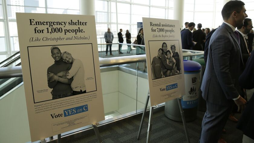 Signs urge support for Proposition C at a SPUR luncheon in San Francisco on Oct. 30. The measure on San Francisco's ballot Tuesday would levy an extra tax on hundreds of the city's wealthiest companies to raise $300 million for homelessness and mental health services.