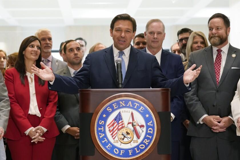 Rodeado por legisladores, el gobernador de Florida, Ron DeSantis, habla al final de la sesión legislativa en el Capitolio en Tallahassee, Florida, 30 de abril de 2021. (AP Foto/Wilfredo Lee)