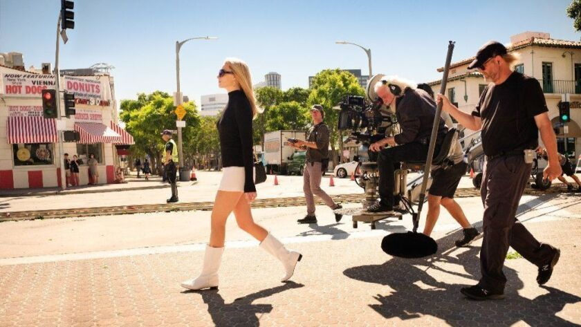 """Margot Robbie as Sharon Tate, plus crew members with equipment for """"Once Upon a Time ... in Hollywood."""""""