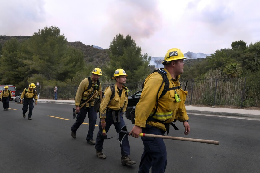 A fire crew walks in line to fight the Palisades Fire in the Pacific Palisades area of Los Angeles, Sunday, May 16, 2021. (AP Photo/Ringo H.W. Chiu)