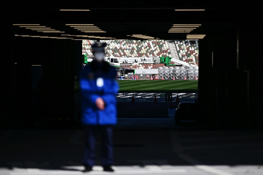 A masked security guard stands in front an entrance to National Stadium, a venue for the 2020 Tokyo Olympics.