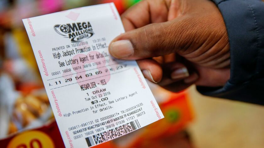 A customer shows a Mega Millions lottery ticket he bought Saturday at a retailer in Washington, D.C.