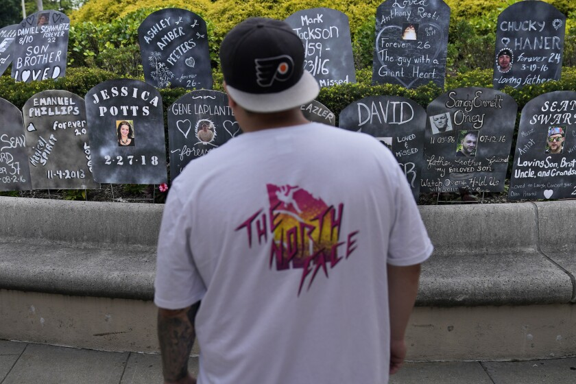 A man looks at cardboard gravestones with the names of victims of opioid abuse outside the courthouse where the Purdue Pharma bankruptcy is taking place in White Plains, N.Y., Monday, Aug. 9, 2021. Purdue Pharma's quest to settle thousands of lawsuits over the toll of OxyContin is entering its final phase with the grudging acceptance of most of those with claims against the company. A confirmation hearing is to open in U.S. Bankruptcy Court on Thursday for a deal that removes control of the company from members of the wealthy Sackler family and requires them to contribute $4.5 billion to opioid abatement While most states and others with claims have signed on, there's still deep anger that Sackler family members would receive protection from lawsuits under the deal. (AP Photo/Seth Wenig)