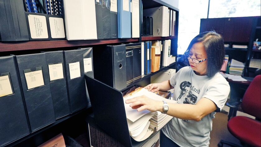 Senior Accountant Winnie Fung scans through files, looking for when the city purchased the building
