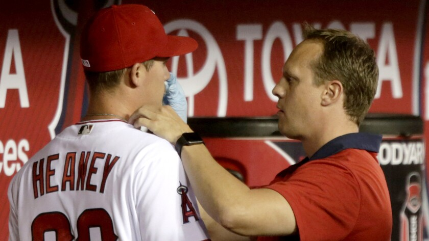 Angels trainer Adam Nevala tends to the bloody nose of pitcher Andrew Heaney in the middle of the second inning during a game April 5.