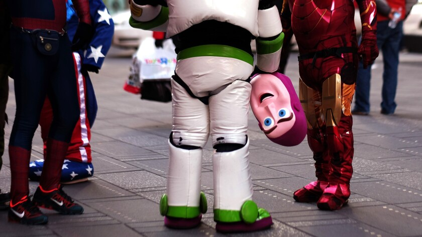 """""""Buzz Lightyear"""" holds his mask while standing with other costumed superheroes and cartoon characters at Times Square in 2015"""