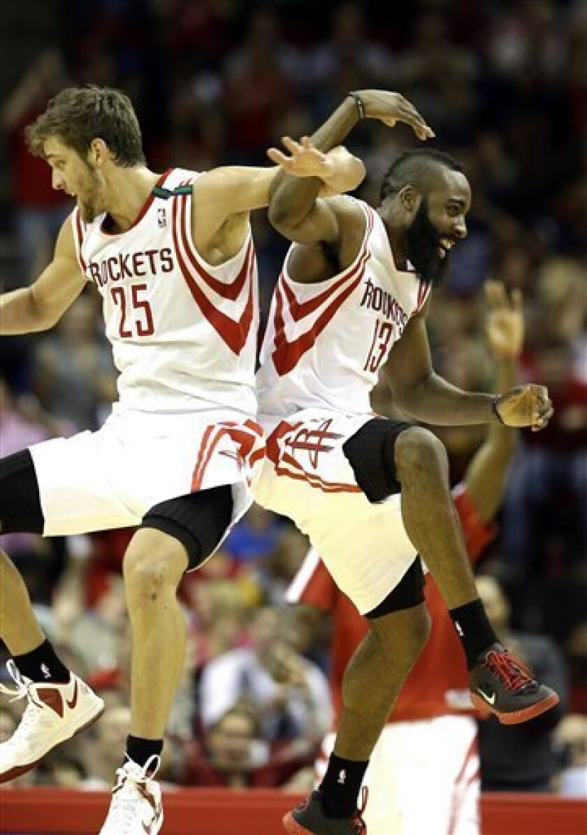Houston Rockets' Chandler Parsons (25) and James Harden (13) celebrate during a timeout after teammate Toney Douglas hit a three-point shot during the fourth quarter of an NBA basketball game against the Boston Celtics Friday, Dec. 14, 2012, in Houston. The Rockets beat the Celtics 101-89. (AP Phot